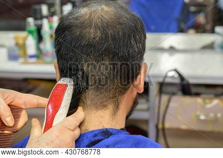 Rear View Of Asian Man Getting Haircut By Hairdresser At The Barbershop. Haircut Refers To The Styli
