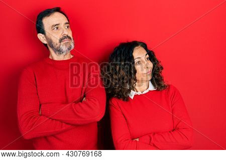 Middle age couple of hispanic woman and man hugging and standing together looking to the side with arms crossed convinced and confident