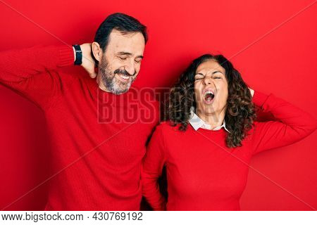 Middle age couple of hispanic woman and man hugging and standing together suffering of neck ache injury, touching neck with hand, muscular pain