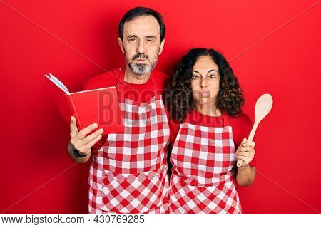 Middle age couple of hispanic woman and man wearing professional apron reading cooking recipe book puffing cheeks with funny face. mouth inflated with air, catching air.