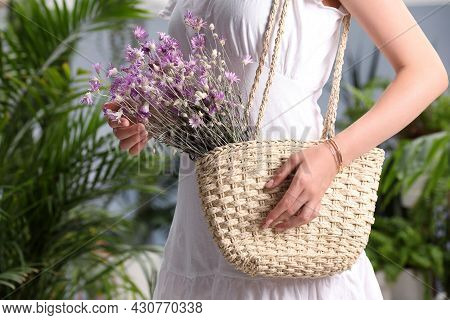 Woman Holding Beach Bag With Beautiful Bouquet Of Wildflowers Indoors, Closeup