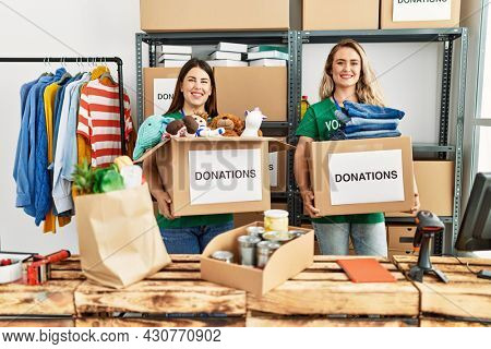 Two young volunteers woman holding donations boxes working at charity center.
