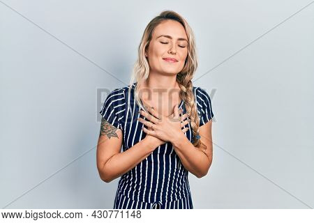 Beautiful young blonde woman wearing casual striped dress smiling with hands on chest with closed eyes and grateful gesture on face. health concept.