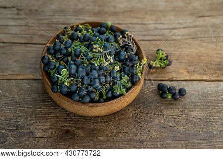 Black Nightshade Berries In A Plate On Table Close-up. Nightshade In Cooking. Healthy Food. Harvest