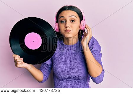 Young hispanic woman using headphones holding vinyl disc puffing cheeks with funny face. mouth inflated with air, catching air.