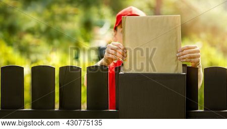 Postman Mail Carrier Inserting Blank Postal Envelope Into Mailbox Over The Fence. Banner Copy Space