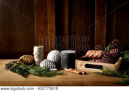 Christmas decorations, evergreen twigs, cones, candle and twine on rustic wooden table. DIY Christmas decoration