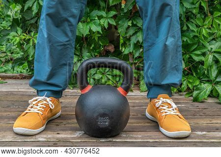 backyard fitness concept - weight training with a heavy iron competition kettlebell on a wooden patio
