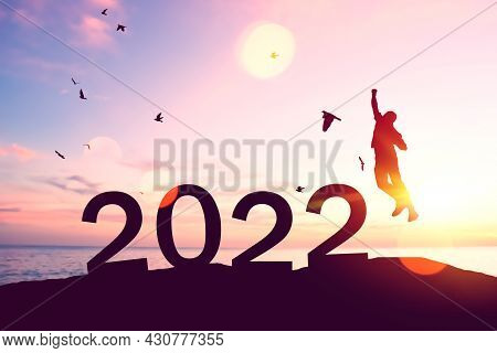 Silhouette Man Jumping And Birds Flying With Number Like 2022 At Tropical Beach On Sunset Sky Abstra