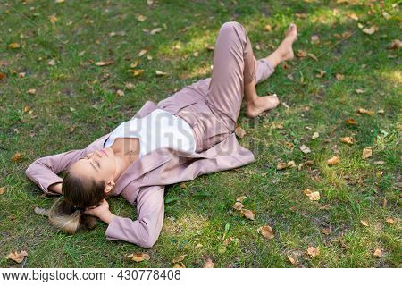 Pensive Young Woman Lies In The Park On The Grass With Closed Eyes - Digital Detox Concept.