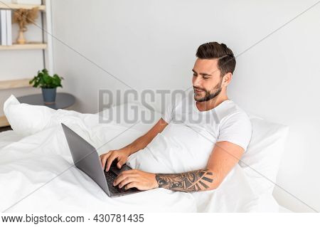 Job In Bedroom, Surfing, Browsing On Internet. Happy Millennial Man Woke Up, Sitting On White Bed, F