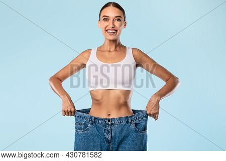 Woman Pulling Her Old Large Loose Jeans And Posing