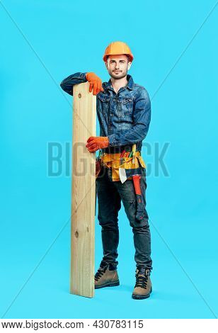Full Length Portrait Of Young Handsome Carpenter Hold Pile Of Lumber Woods