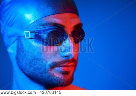 Close Up Portrait Of Handsome Swimmer With Goggles In Red-pink Neon Light Over Blue Background
