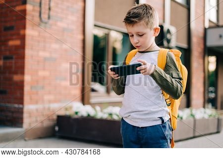 Back To School. Cute Child With Backpack And Mobile Phone Going To School. Boy Pupil With Bag. Eleme