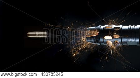 Copper Bullet Just Flying Outside The Sparks And Smoke After A Shot From An Ar-15 On A Black Backgro