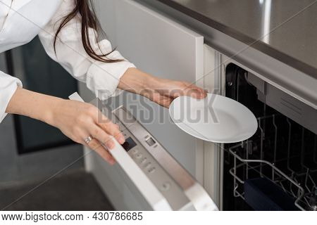 Cropped Shot Of Woman Using Modern Built-in Dishwasher Machine While Doing Housework In Kitchen At H