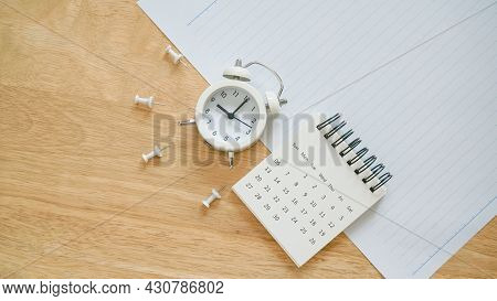 White Calendar, Thumbtack And Analog Alarm Clock On School Paper With Line On Wooden Desk For Back T