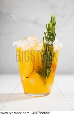 Fresh Cold Peach Drink In Glass With Ice Cubes, Green Rosemary, Fruit Slice, Sugar Rim In Soft Light