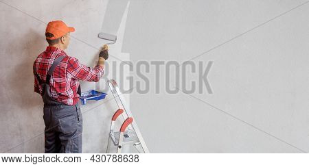 Professional Painter Man Painting Wall In Grey Color. Banner. Repair Home Concept.
