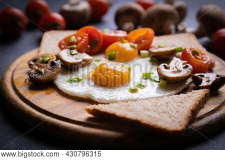 Sunny side up fried eggs with mushrooms and cherry tomato