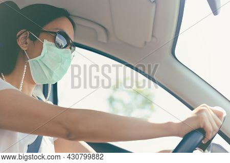 Woman Driving Car With Medical Mask And Sunglasses On Her Face. Health Care And Virus Protection