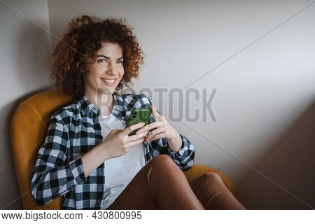 Woman With Curly Hair On Armchair Is Using Phone. Pretty Young Woman. Online Education. Internet Tec