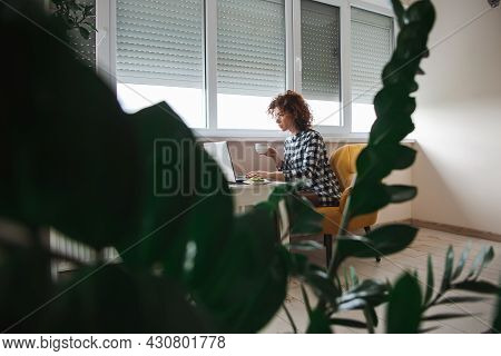 Woman At Home Using Laptop. Mobile Communication. Online Communication. Curly Hair. Coffee Break. In
