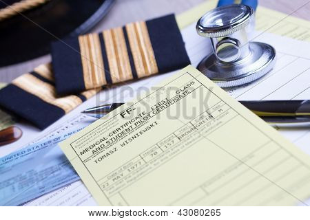Close up of an airplane pilot equipment hat and epaluetes with medical and pilot certificate, stethoscope and pen. Conceptual image of medical exam.