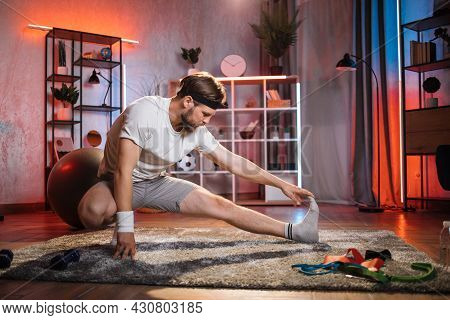 Middle Aged Bearded Man Stretching Body On Floor. Caucasian Guy Wearing Casual Clothes, Socks And He
