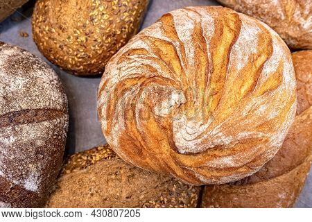 Round Loaf Of Bread On Background Of Different Bread Loaves. Bread Collection Top View Background.