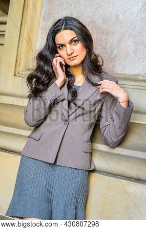 Dressing In A Gray Jacket And Skirt, A Young Businesswoman Is Standing Outside Against A Wall, Liste