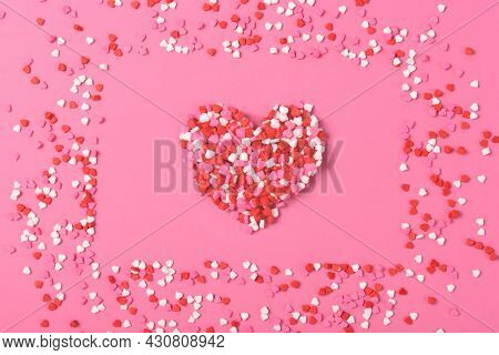 A heart shape made from heart shaped candy surrounded by a frame made of the same candies. Valentines Day Concept.