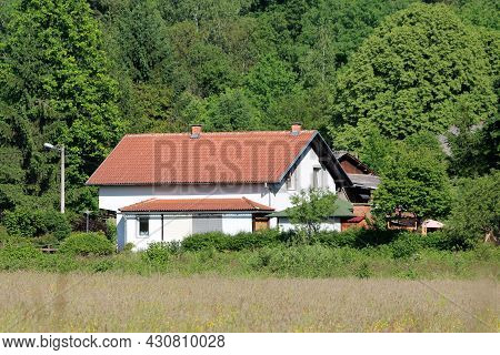 Freshly Renovated Small Suburban Family House With New Roof Tiles And White Facade Surrounded With D