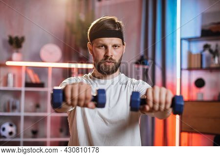 Portrait Of Active Bearded Man Exercises With Dumbbells During Evening Time. Caucasian Beginner In S