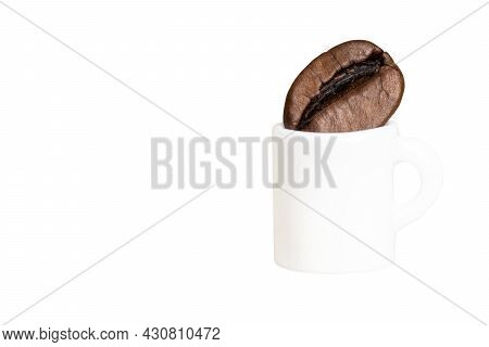 Miniature Coffee Cup With A Coffee Bean Isolated On White. Sense Of Proportion.