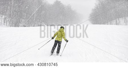 Alpine ski during snowstorm. Woman athlete skiing downhill on snowy slope in cold weather. Banner panoramic of winter sport.