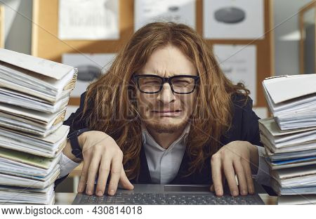 Funny Unhappy Office Worker Sitting At Desk And Crying Stressed By Huge Workload