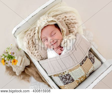 Little beautiful newborn baby girl wearing hat sleeping under handmade blanket in tiny designed bed and smiling during studio photoshoot. Cute infant child kid napping resting