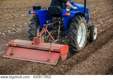The Tractor Is Cultivating The Soil In The Farm Field. Freeing Milling Earth Ground From Old Crops.