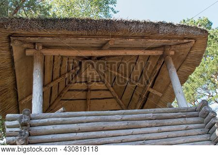 Vintage Log Timbered Wooden Watchtower With A Thatched Roof On The Background Of Blue Sky And Overha