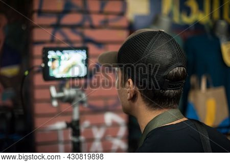 Behind The Scenes. Film Director Oversees And Control The Shooting Of The Film On The Lcd Panel From