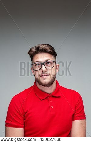 Handsome Friendly Young Man In Glasses Looking Up. Vision Correction By Spectacles, Myopia, Ophthalm