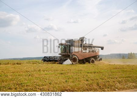 Old Harvester Plows The Field. Harvester Harvests Wheat From A Sown Agricultural Field Summer Day