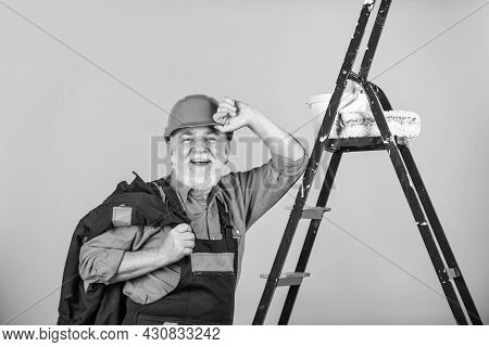 Time To Relax. Painter Working At Construction Site. Senior Man Use Roller On Ladder. Work In Apartm