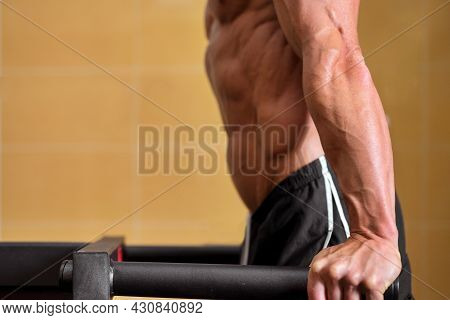 Close Up Of A Muscular Man Doing Triceps Dip On Parallel Bars In Gym. High Quality Photo.