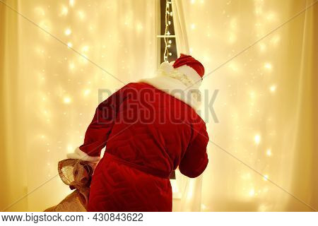 Santa Claus Looks Out Window And Waits For Arrival Of A Sleigh Pulled By Deer. Animator Or Parent In