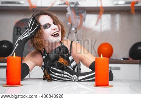 Young Woman In Skeleton Costume Hugs Cute Dachshund Puppy And Laughs, Leaning Her Head On Hand, And