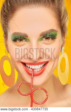Beauty and pin-up style. Close-up portrait of an attractive girl with bright makeup drinking soda on a yellow background. Make-up and cosmetics.