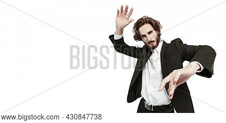 Fashion concept. Portrait of a handsome well-groomed man fashion model posing in motion at studio. White background with copy space.